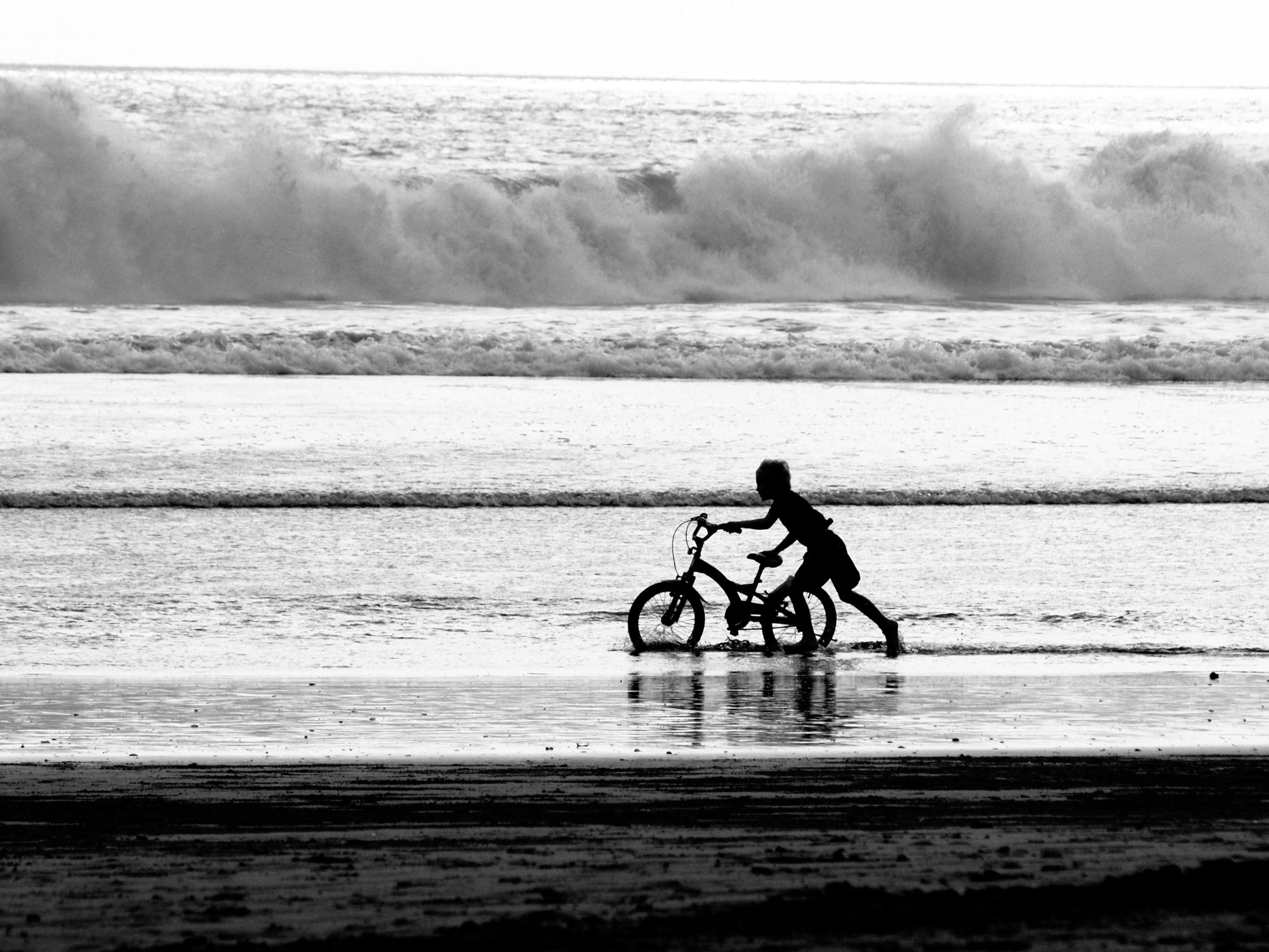 boy pulling bicycle on lake during daytime
