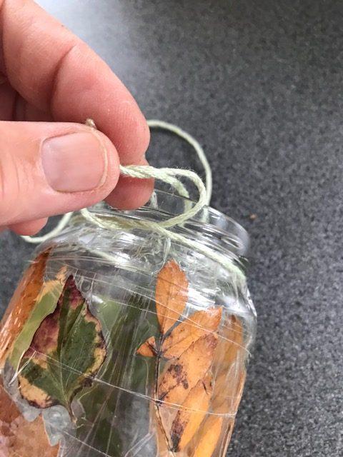 Put dried leaves on a jar and wind sellotape around the jar to keep them in place.