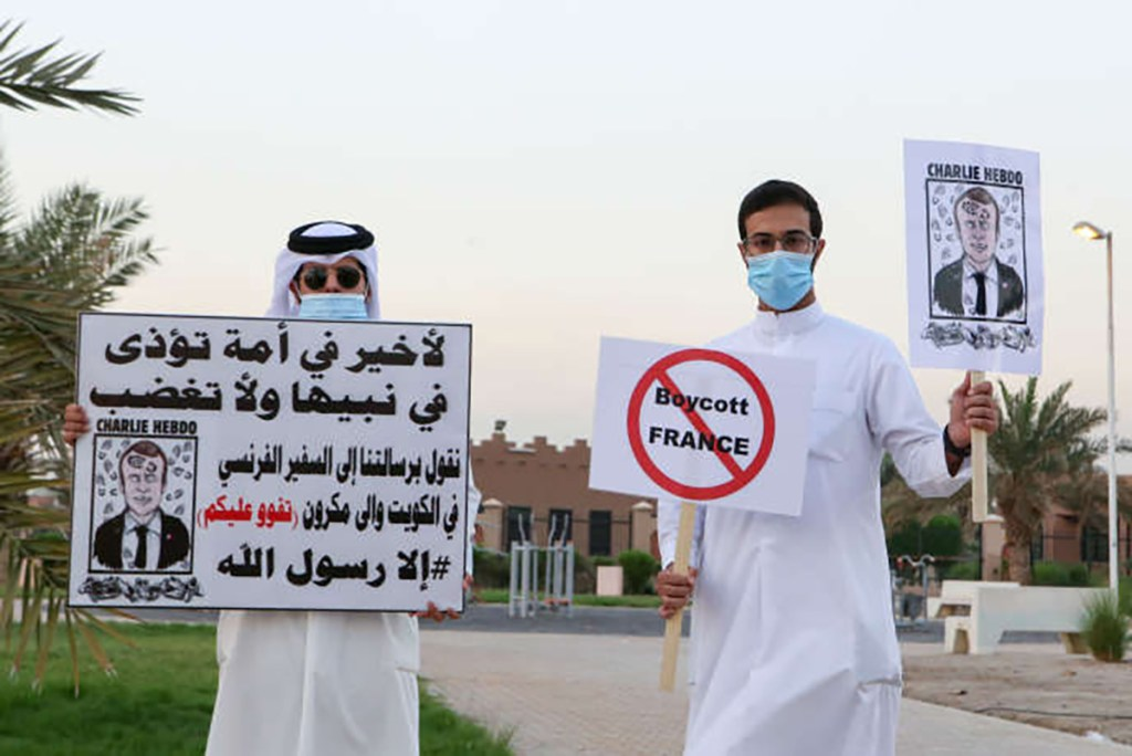 Kuwaitis lift placards expressing anger at French President Emmanuel Macron at a rally in front of the country's National Assembly (parliament) in Kuwait City, on October 24, 2020. Several Middle Eastern countries have slammed comments by President Emmanuel Macron defending cartoons of the Prophet Mohammed, with some instituting boycotts of French goods. / AFP / -
