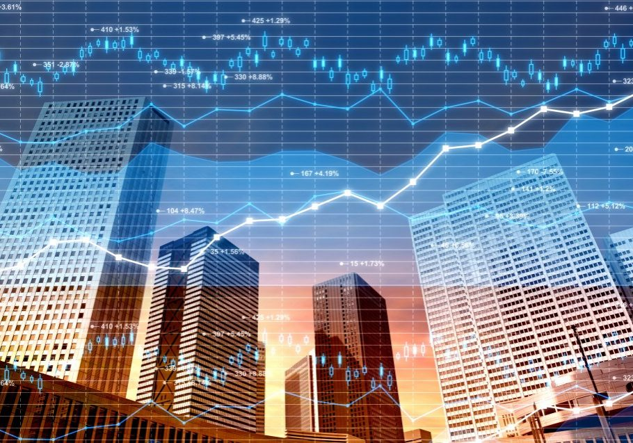 Panorama of a city business district with office buildings and skyscrapers and superimposed data, charts and diagrams related to stock market, currency exchange and global finance. Blue line graphs with numbers and exchange rates, candlestick charts and financial figures fill the image with a glowing light. Sunset light.