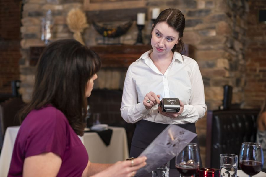 PointofSale Waitress using pay at the table device at table Pay at the table