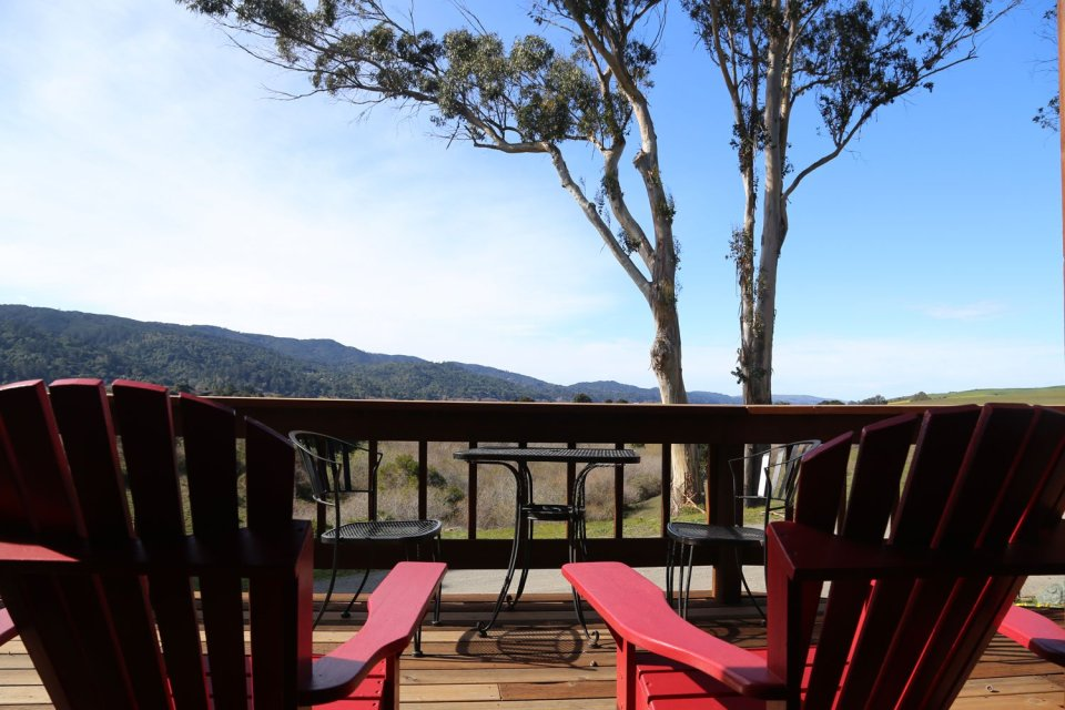 View of mountains and sky and tree and deck chairs on the deck of Black Heron Inn in Point Reyes.