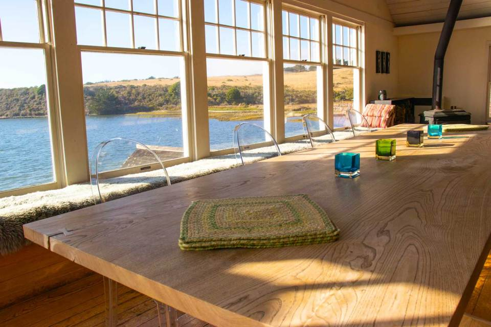 View of Tomales Bay from dining room with large windows and long dining table.