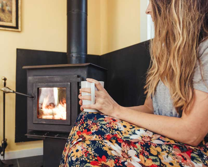 Woman holding coffee cup in front of a wood burning fireplace.