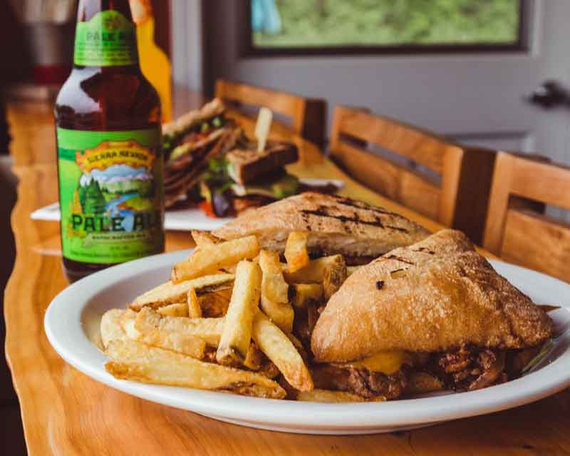 Sandwiches and fries on the counter, with a bottle of beer.