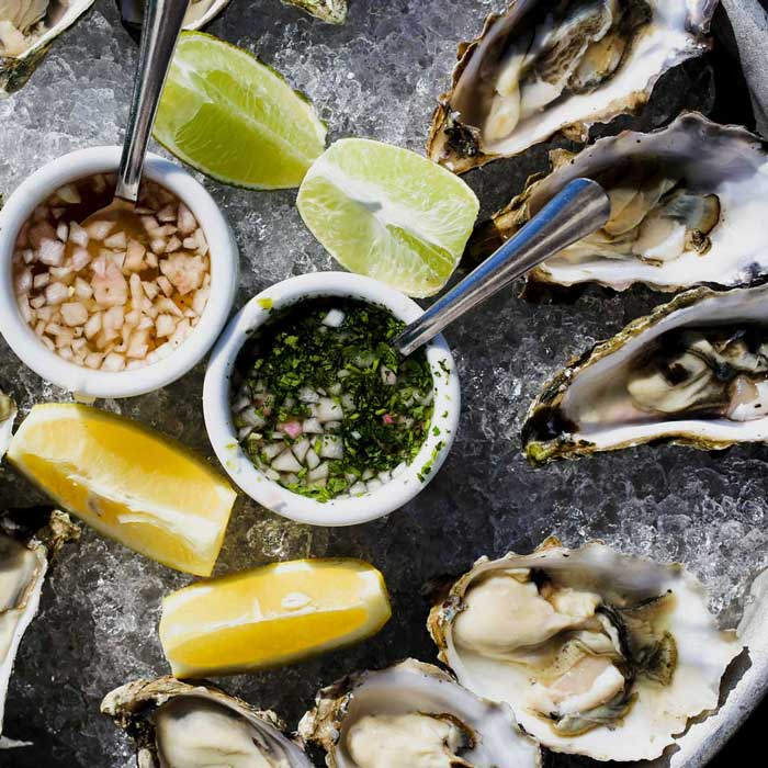 Raw oysters on ice with sauces.