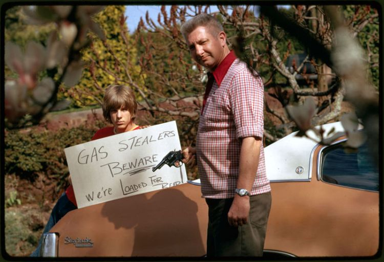 Father and son hold up their sign saying Gas Stealers beware during the 1973 Oil Crisis