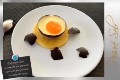 Œuf glacé dans sa coquille au chocolat, posé sur une génoise au sirop d'orange
