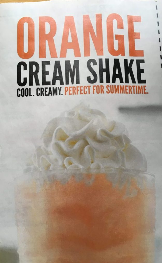 Large glass of orange liquid topped with whipped cream, claiming to be an orange cream shake