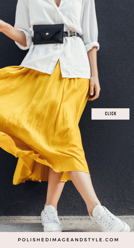 Stylish woman is yellow skirt, white button down and black belt bag