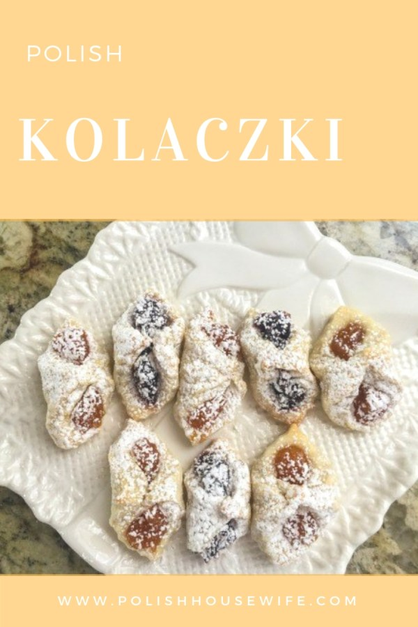 fruit filled kolaczki cookies on a white plate on a granite slab