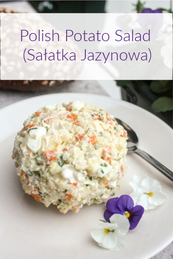 polish vegetable salad on plate with small pansy flowers