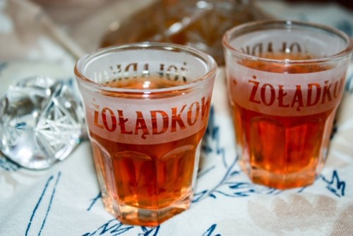 two shot glasses of zoladkowa gorzka on a patterned cloth with a small crystal decantor in the background