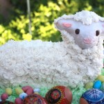 Easter lamb cake on green coconut with decorage eggs in foreground