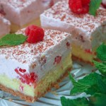 cheesecake topped with raspberry mousse garnished with raspberry and mint