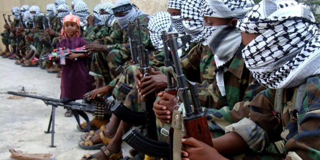 A Somali boy holding a toy gun surrounded by al-Shabab members