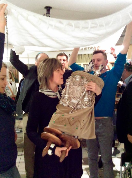 Dr. Halina Postek, lead teacher of Step-by-Step, and professor at Warsaw University surrounded by her students carries the Torah to the Ark