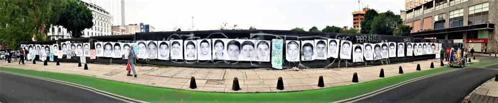 Carteles con los rostros de los 43 colocados entre la avenida Paseo de la Reforma y la calle Juárez, frente al Monumento a Colón en la Ciudad de México a 43 meses de la desaparición forzada de los normalistas, 26 de abril de 2018 | Fotografía de Martín López Gallegos.