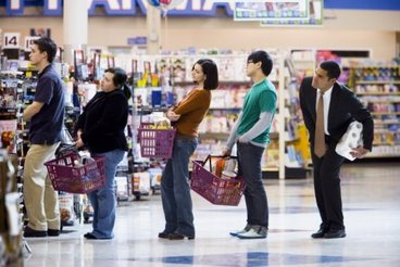 People waiting in line with shopping baskets at grocery store