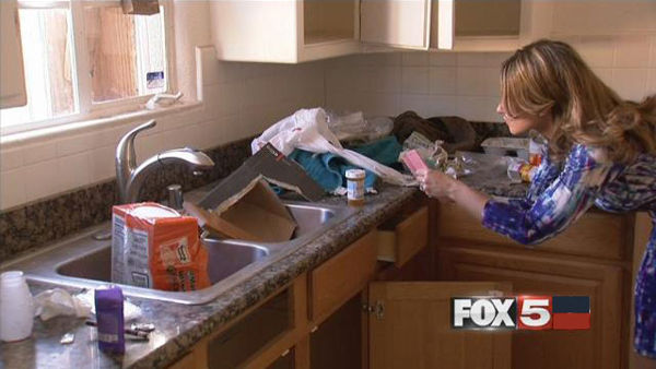 Realtor Ashley Hawks takes closer look at debris and leftover packaging following the eviction of squatter at one of her listed properties. (Ophelia Young/FOX5)