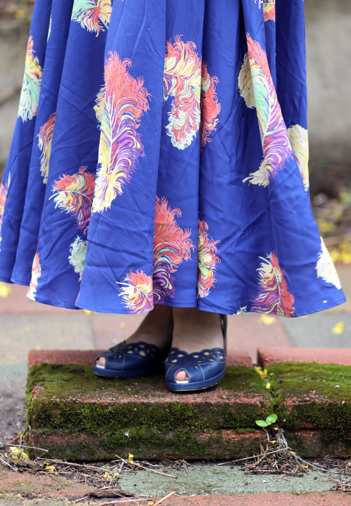 Deep blue leather 1940s styled shoes with a small peep-toe and cut-out vamps peek out from under the hem of a cobalt blue dress with feathers on it