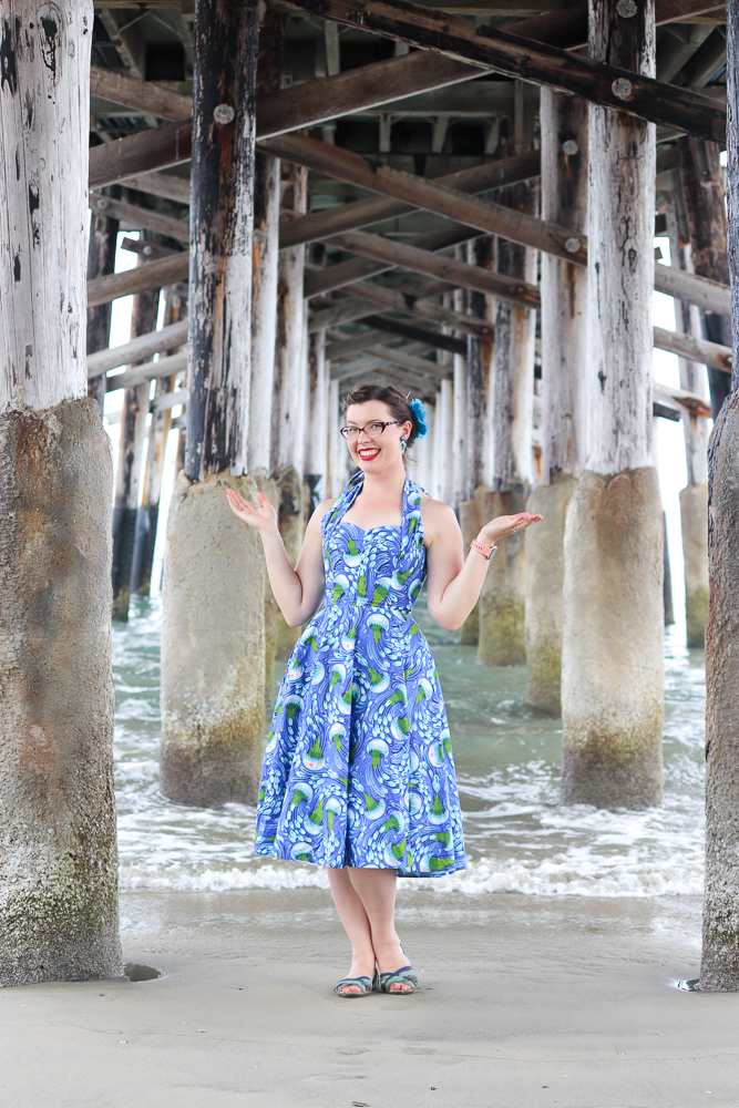 A girl stands under a pier wearing the Charm Patterns Lamour Dress in a blue jellyfish cotton with the straps tied in a conventional halter