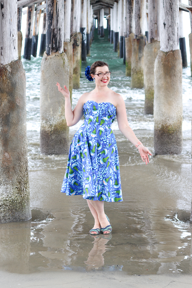 A girl stands under a pier wearing the Charm Patterns Lamour Dress in a blue jellyfish cotton with the straps tied behind for a strapless effect