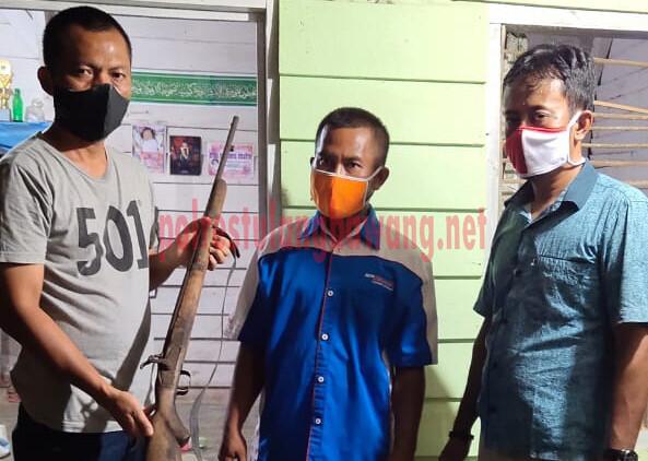 PS. Kanit Reskrim dan PS. Kanit Intelkam Polsek Penawartama saat menerima senpi rakitan laras panjang jenis locok dari Ketua RK di Kampung Sidomulyo