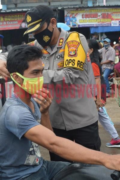 Kapolres Tulang Bawang AKBP Andy Siswantoro, SIK saat membagikan masker di Pasar Unit 2, Kampung Dwi Warga Tunggal Jaya