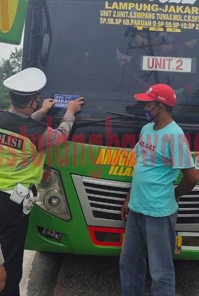 Personel Satlantas Polres Tulang Bawang saat memasangkan stiker imbuan ayo pakai masker pada kendaraan umum mobil bus yang melintas di Jalintim