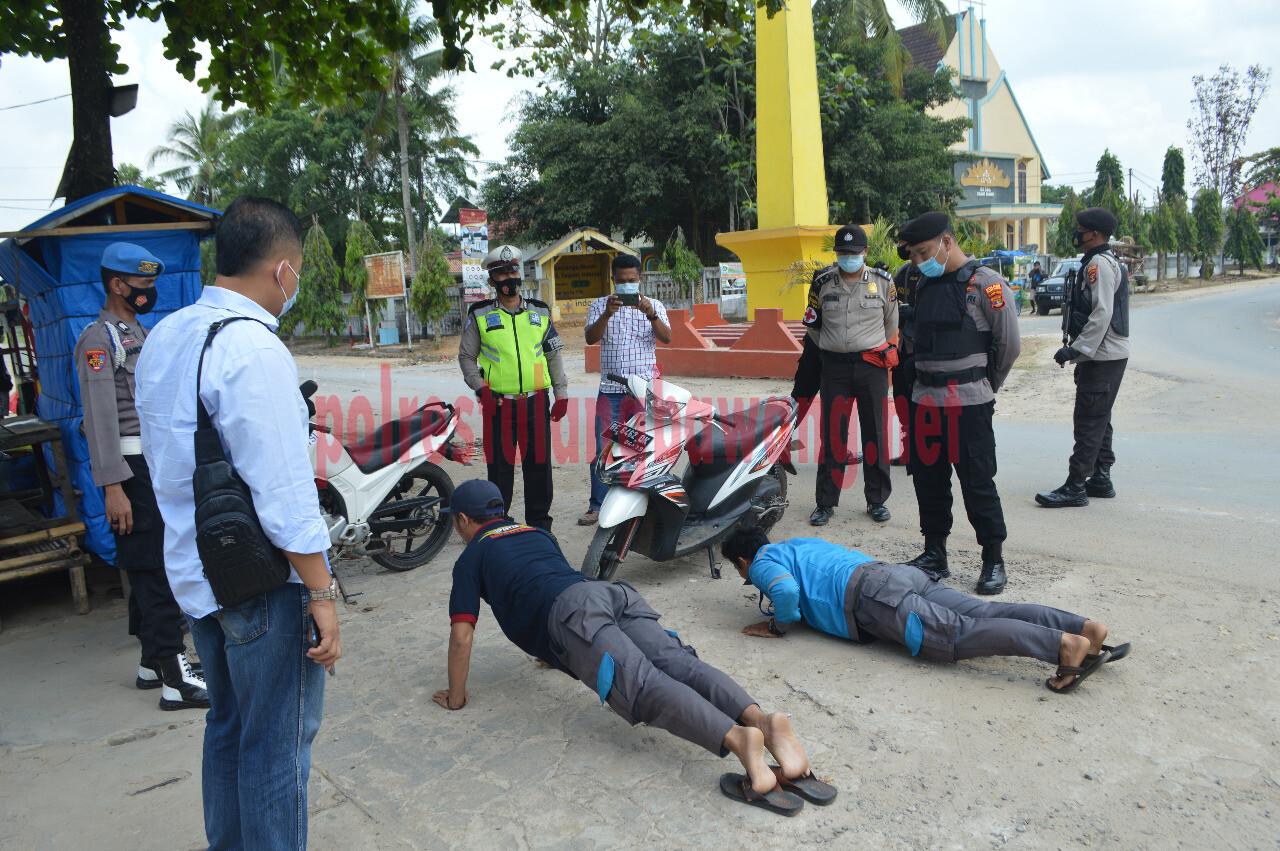 Dua orang karyawan PLN menerima sanksi push up saat terjaring Operasi Yustisi Polres Tulang Bawang di Tugu Kuning, Kampung Tri Tunggal Jaya, Kecamatan Banjar Agung