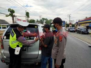 Personel Satlantas Polres Tulang Bawang sedang memasang stiker imbauan ayo pakai masker di kendaraan pribadi saat menggelar Operasi Zebra Krakatau-2020 di Jalintim, Kampung Lebuh Dalem