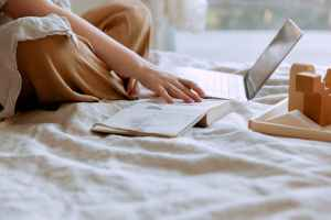 woman using a laptop on a bed