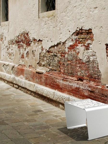 Le tabouret LUD gris présenté devant un mur abîmée, dont on voit les briques