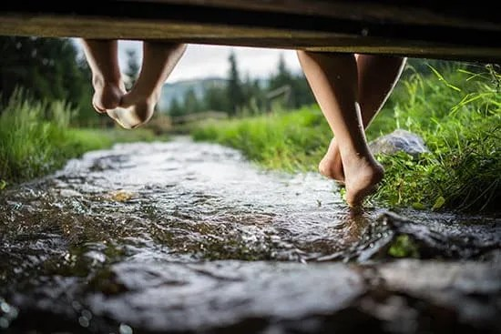 children's feet swinging under dock, above stream