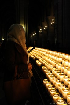 In front of the votive candles of Notre Dame. © Violet Acevedo