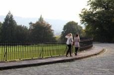 Women walking along the Royal Crescent and looking at Royal Victoria Park. © Violet Acevedo