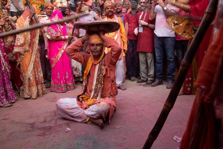 Men being beaten with sticks during Lathmar Holi