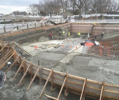 Wet mix shotcrete being installed on a commercial swimming pool on the coast of New York. The nozzleman is installing new strips of shotcrete while other finishers are working on a wall on the left. In the foreground is an unfinished area that will have large stairs, so finishing was unnecessary.