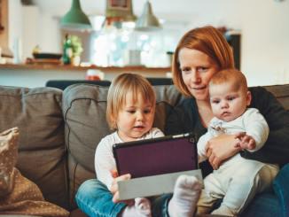 Une mère et ses deux enfants manipulant une tablette.