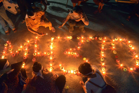 Cambodian residents of a community light candles as they pray for the missing Malaysia Airlines flight MH370 at their village in Phnom Penh on March 17, 2014.