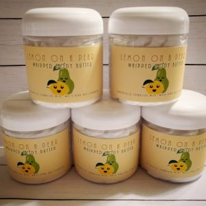 """Stack of 5 jars of whipped body butter. The label is yellow with a smiling faced lemon and pear on it. Text above reads """"Lemon On A Pear Whipped body Butter"""""""