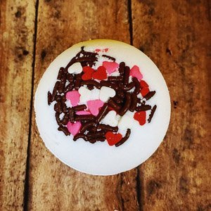 Round white bath bomb with a mixture of brown, white, red and pink heart sprinkles on top