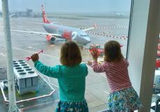 twins looking out of the airport window at the plane