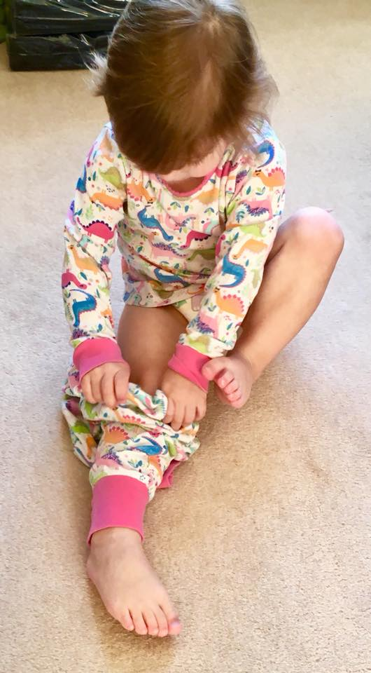 child putting on her pyjamas without help