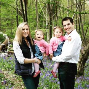 A family standing in the woods for a bluebell photoshoot