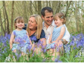 A family with twin girls sitting in the bluebells