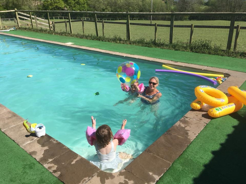 The Popitha Twins swimming with mum and dad in the swimming pool at North Bradbury Farm