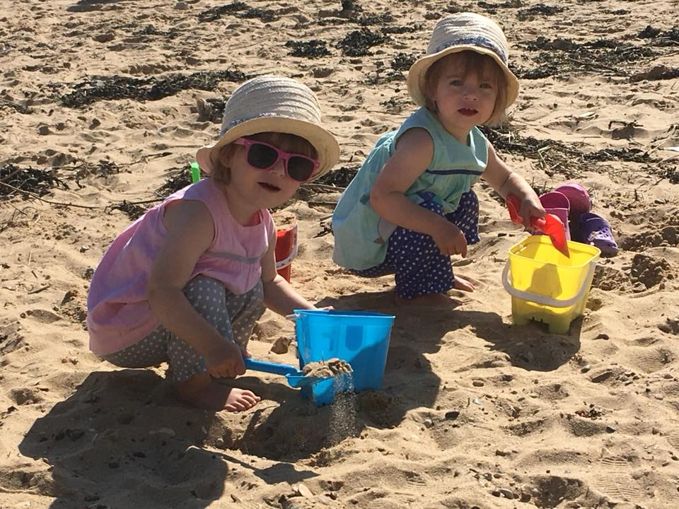 twins on holiday playing on the beach