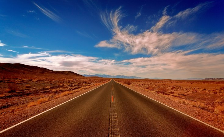Car going on a long journey down an open road